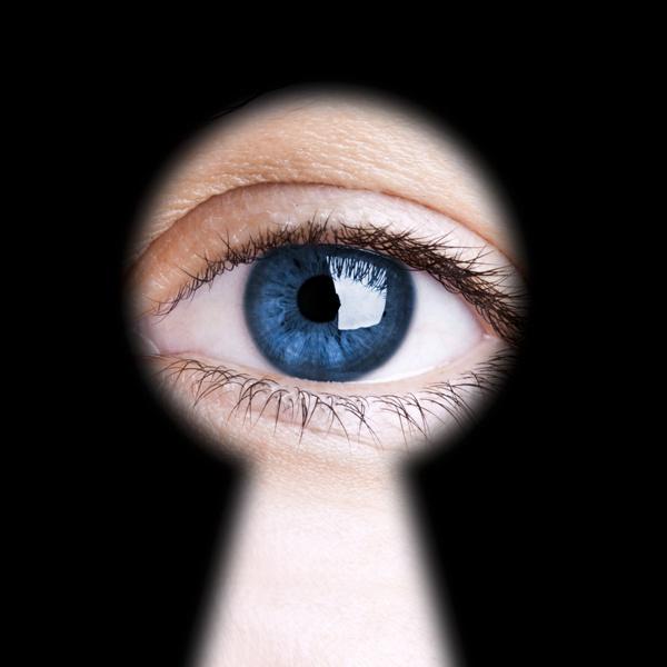 Eye looking through a blured black keyhole